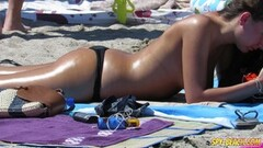 Gorgeous babes sunbathing at the beach Thumb