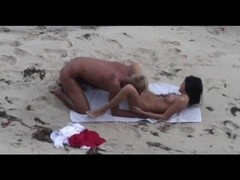 Young couple caught on the beach Thumb